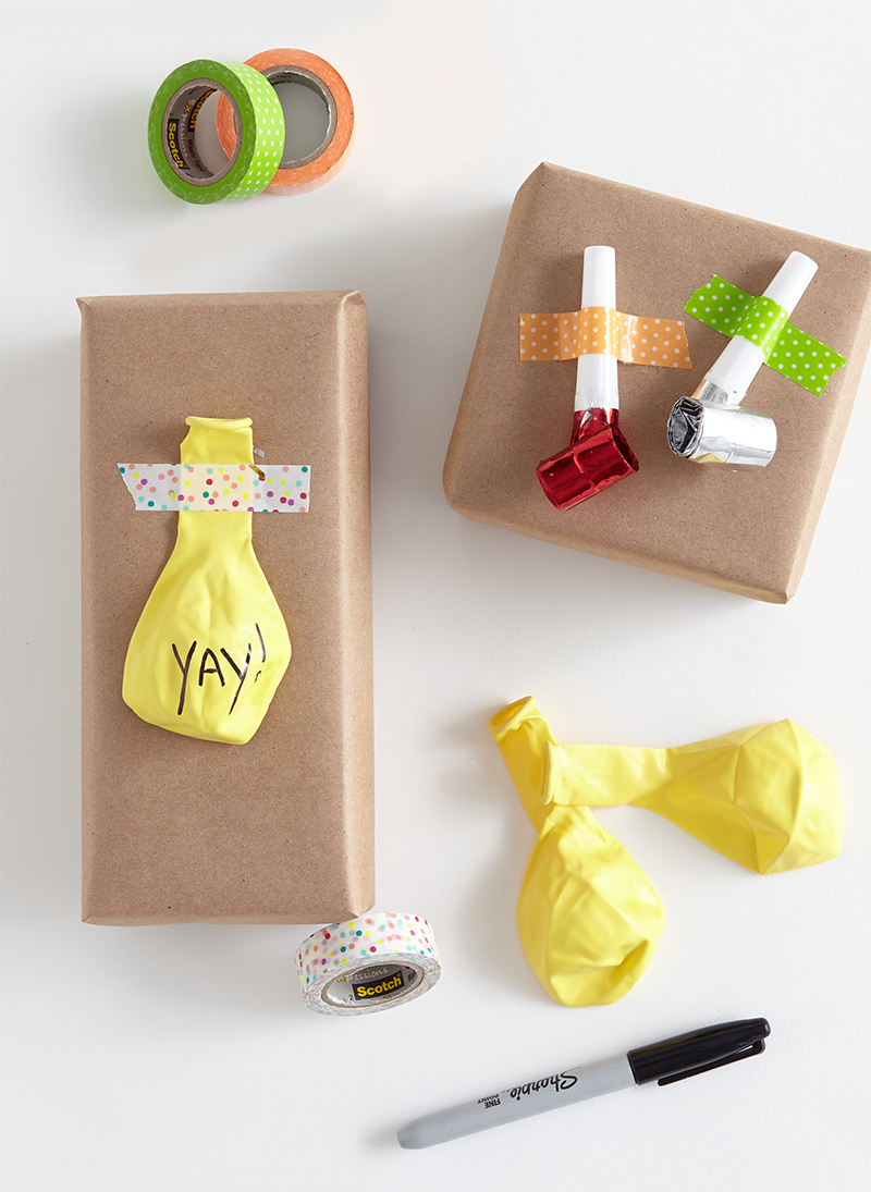 balloons and blowout noise makers taped to top of brown paper wrapping