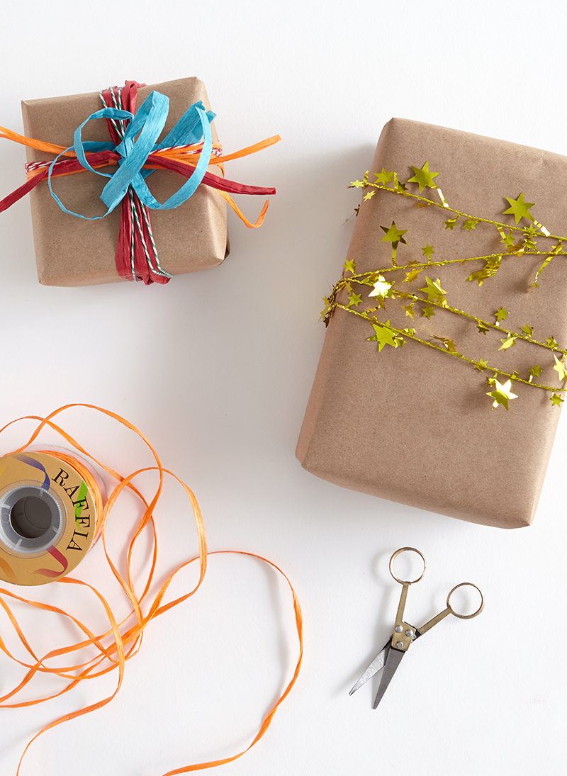 gold star tinsel garland wrapped around brown wrapping paper