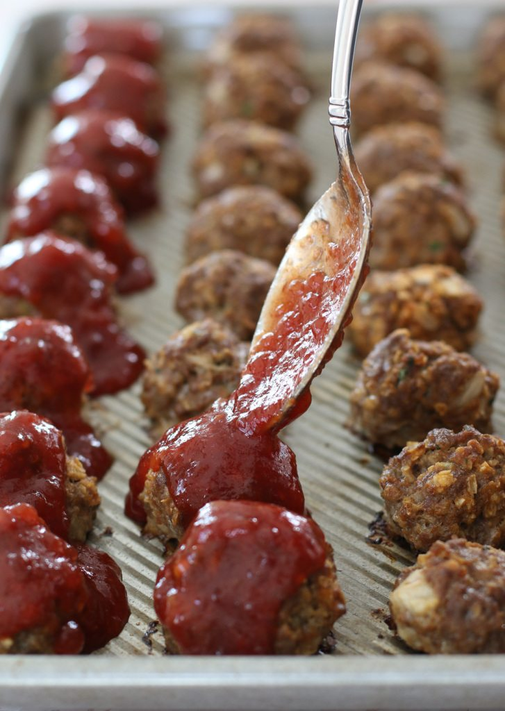 spooning cranberry sauce on meatballs