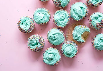 cup cakes on pink background with blue frosting